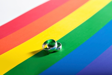 Two silver rings resting on a background in colors of a homosexual flag